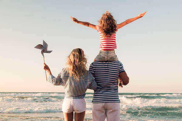 Glückliche Familie mit Kind am Strand blickt auf das Wasser