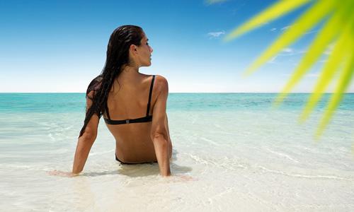 Frau sitzt im Bikini am Strand 500x300