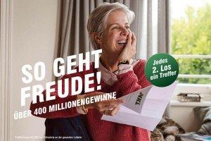 Glückliche Frau am Kaffeetisch mit NKL-Gewinnbescheid 600x400